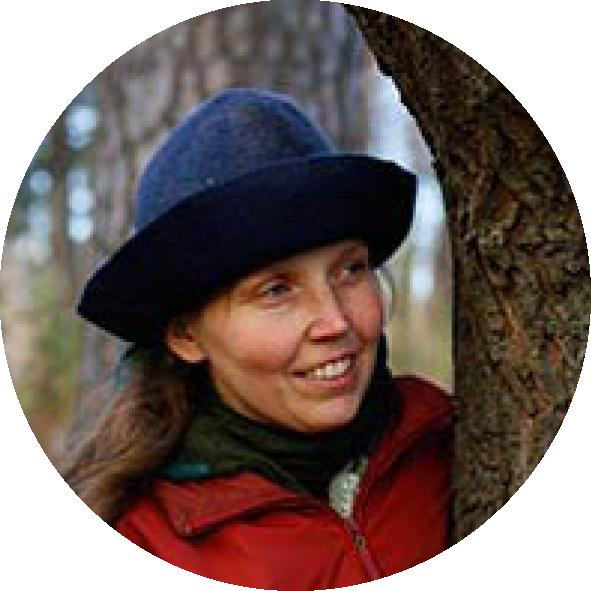 Ympäristökasvatjja Milla Tuormaa hattu päässään kurkkaa puunrungon takaa.