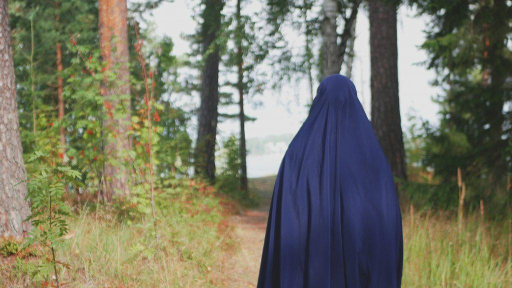 Huntupäinen nainen kävelee suomalaisessa mäntymetsässä.