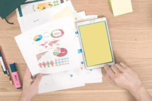 henkilö pitelee kädessä paperista infograafia, vieressä padlet