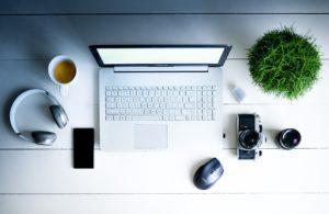 pöydällä kannettava tietokone, kuulokkeet, hiiri