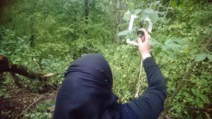 nainen burkhassa tutkimassa luupilla puun lehtiä.