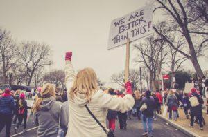 """nainen mielenosoituksessa, naisen kyltissä lukee """"we are better than this"""""""