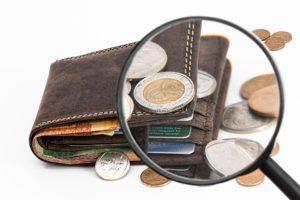 Suurennuslasissa näkyy lompakko, josta pursuaa rahaa
