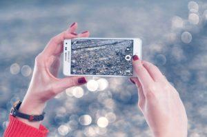 naisen kädet kuvaamassa kännykällä, kännykästä näkyy kivinen ranta