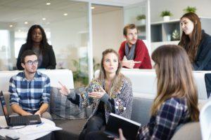 Nuoria ihmisiä istumassa pöydän ympärillä, läppäri pöydällä, keskustelemassa.