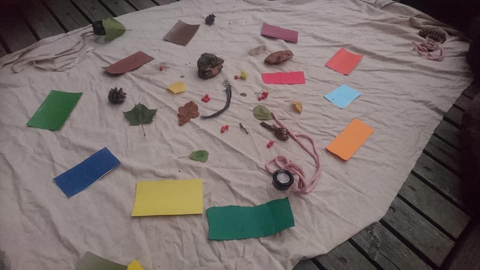 Värikkäitä papereita, luonnon esineitä ja luuppeja kankaalla.