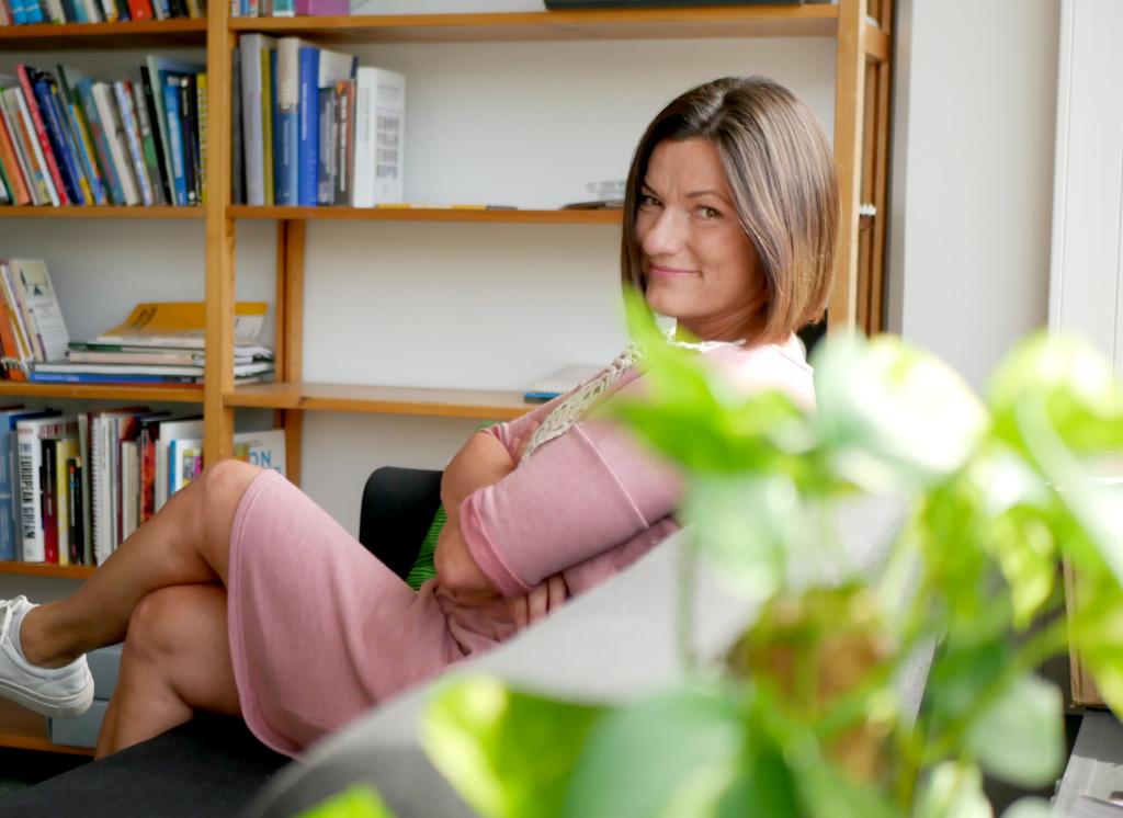 Katja Alvoittu istuu vaaleanpunaisessa mekossa sohvalla Vision kirjastossa.